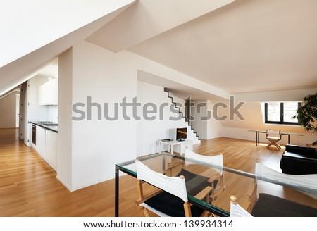 Interior, beautiful loft, hardwood floor, dining table - stock photo
