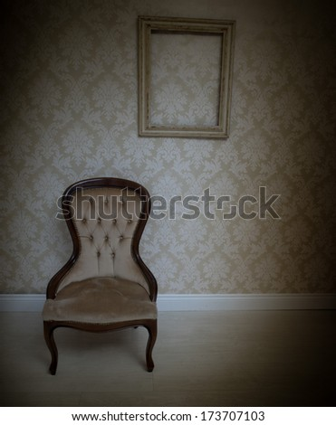 Interior decor background with a vintage upholstered chair standing below an empty wooden picture frame on a wallpapered wall with a retro arabesque pattern in beige with heavy corner vignetting