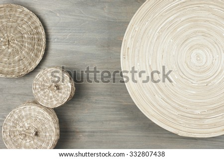 Interior decor: natural wooden dish and baskets on gray shabby wood background. Top view point. - stock photo