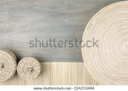 Interior decor: natural wooden dish, mat and baskets on gray shabby wood background. Top view point. - stock photo
