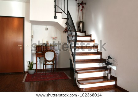 Interior decoration of a room with stairs and antique desk with chair - stock photo