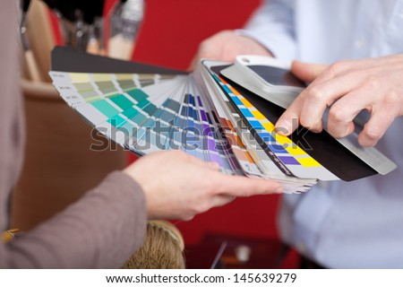 Interior decorator in a meeting with a client discussing various paint colors from a colorful set of swatches he is holding in his hand