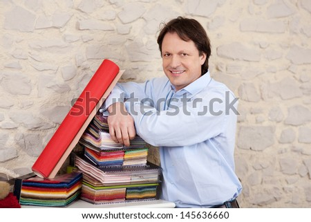 Interior decorator smiling and leaning confidently on a stack of books of fabric samples - stock photo