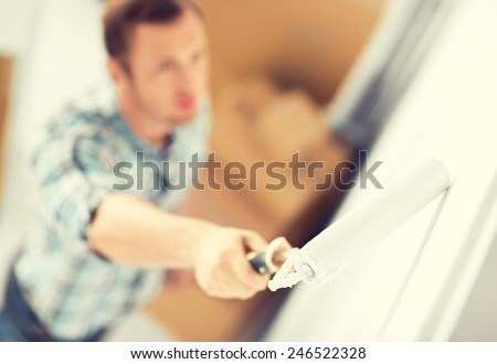 interior design and home renovation concept - man colouring the wall with roller - stock photo