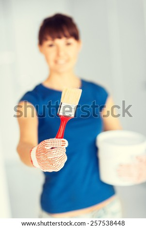 interior design and home renovation concept - woman with paintbrush and paint pot - stock photo