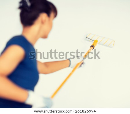 interior design and home renovation concept - woman with roller and paint colouring the wall - stock photo