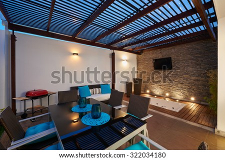 Interior design: Beautiful modern terrace lounge with pergola at sunset - stock photo