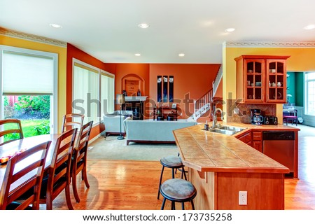 Interior design for kitchen, dining and living room combination. Yellow walls of kitchen and dining room match well with orange color of living room - stock photo