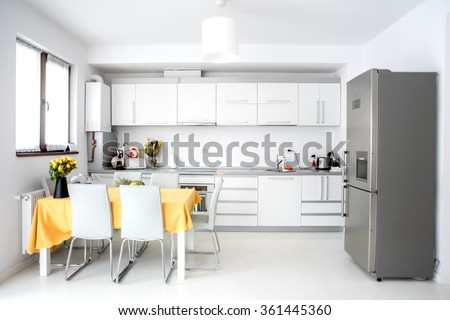 Interior design, modern and minimalist kitchen with appliances and table. Open space in living room, minimalist decor - stock photo