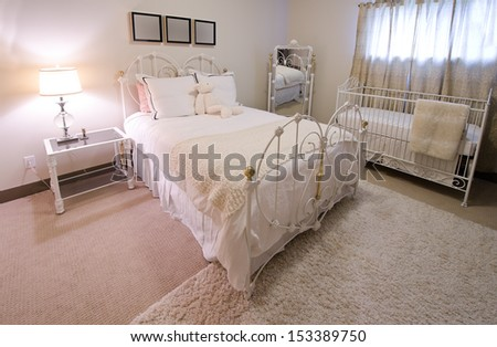 Interior design of a comfortable, stylish and elegant luxury bedroom in retro style with the cradle in the corner. - stock photo