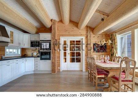 Interior design of a light and comfortable kitchen in a modern wooden log house. - stock photo