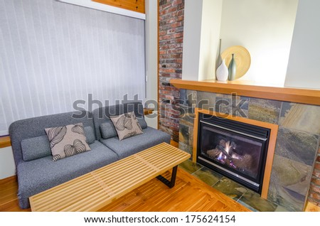 Interior design of a luxury living room with a brick wall and fireplace with a sofa and two pillows