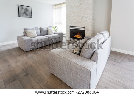 Interior design of a luxury living room with hardwood floors, fireplace and sofas - stock photo