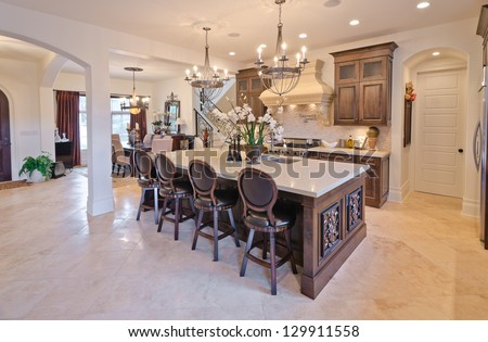 Interior design of a luxury modern kitchen with the counter and some chairs behind. - stock photo
