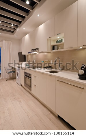 Interior design of a modern kitchen, in combination with laundry and the office room. For small condos. - stock photo