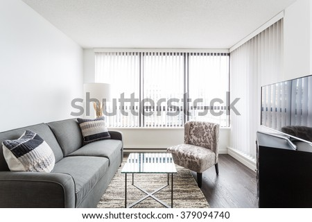 Interior design of a modern living room with hardwood floors, sofa and coffee table. - stock photo
