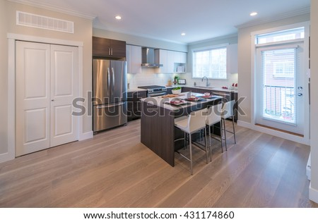 Interior design of luxury modern kitchen with nicely decorated and served kitchen table. - stock photo
