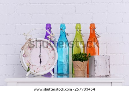 Interior design with alarm clock, plant and decorative colorful glass bottles on tabletop on white brick wall background - stock photo