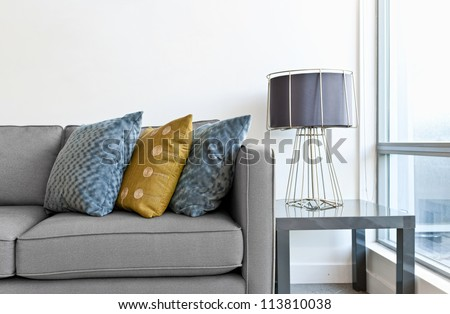 Interior design with couch, colorful cushions and lamp on end table - stock photo