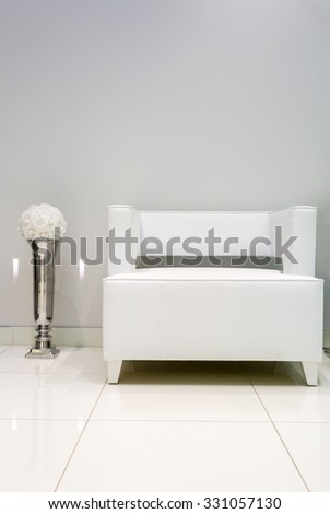 Interior design with white armchair and vase near white wall.  - stock photo