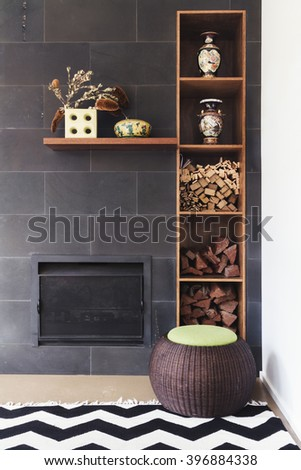 Interior designed living room nook of decor details, fireplace, wood, rug and ottoman - stock photo