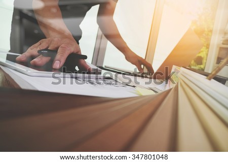 Interior designer hand working with new modern computer laptop and pro digital tablet with sample material board on wooden desk as concept - stock photo