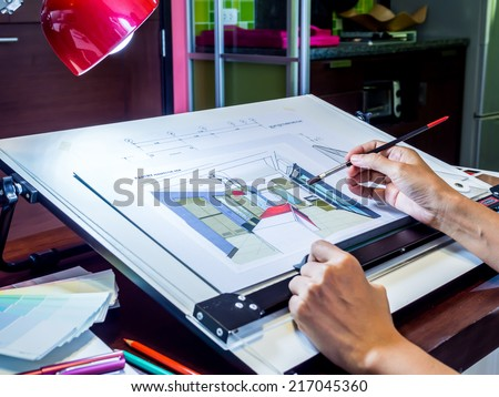 Interior designer's hand working with illustration sketch at modern home office - stock photo