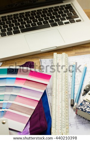 Interior designer's working desktop with architectural plan of the house, keys, color palette guide and laptop - stock photo