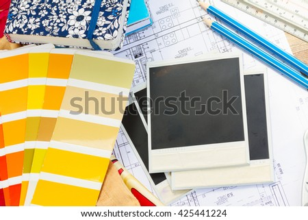Interior designer's working table, an architectural plan of the house,  color palette guide and fabric samples in yellow shades, copy space on instant empty photos - stock photo