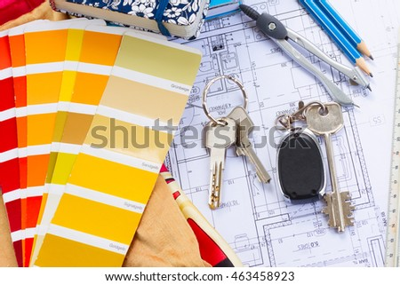 Interior designer's working table, an architectural plan of the house, color palette guide and fabric samples in yellow shades