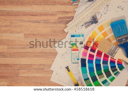 Interior designer's working table with energy rating chart, architectural plan of the house, color palette and brushes, copy space on wooden desktop, retro toned - stock photo