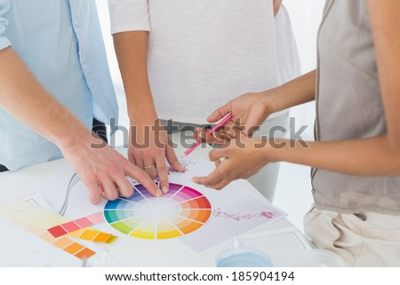 Interior designer showing colour wheel to customers in her studio - stock photo