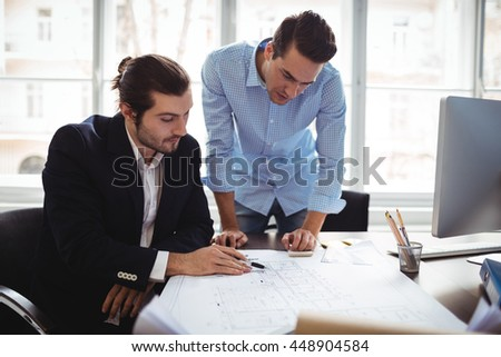 Interior designer with male colleague working on blueprint in office - stock photo
