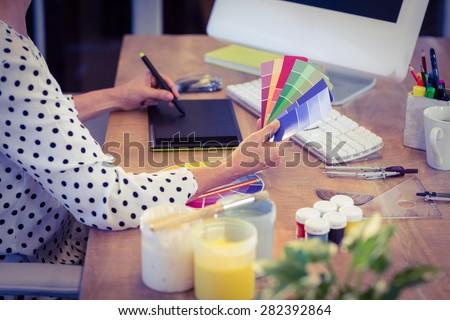 Interior designer working at desk in creative office - stock photo