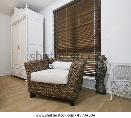 interior detail with vintage wardrobe and rattan armchair - stock photo