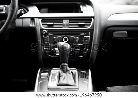 Interior details and elements of modern car, close-up of automatic gearshift knob with cockpit background - stock photo