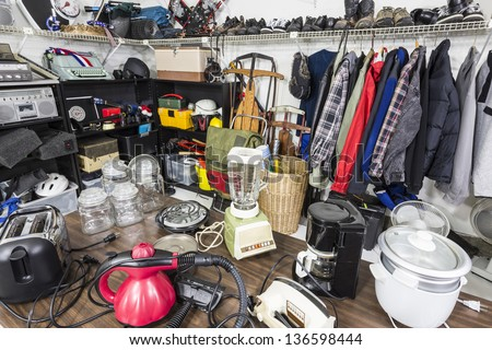 Interior garage sale, housewares, clothing, sporting goods and toys. - stock photo
