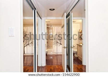 Interior hallway with walk through mirrored closets to bathroom - stock photo