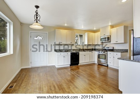 Interior in empty house. Spacious kitchen room with white cabinets and granite tops