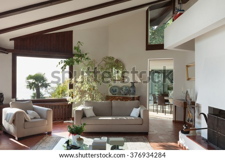 Interior; living room of a rustic house; divan and armchair - stock photo