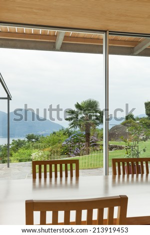 Interior, modern house, garden view from the dining table