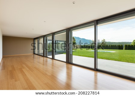 Interior modern villa, wide living room with large windows - stock photo