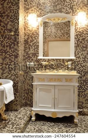 Interior of a bathroom in retro style - bath, mirror and cupboard with washbasin - stock photo
