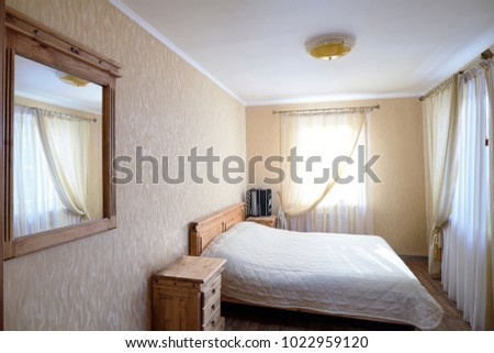 Interior of a bedroom of a rural house with a bayan on a nightstand in pastel tones