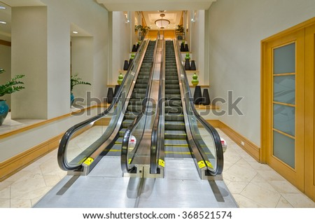 Interior of a building hall. Empty escalator stairs. Fragment of the lobby of the five stars hotel. Interior design. - stock photo