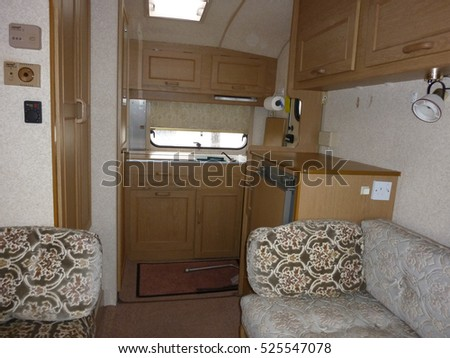 Interior of a classic caravan showing the sofa and cupboards ideal for camping holidays