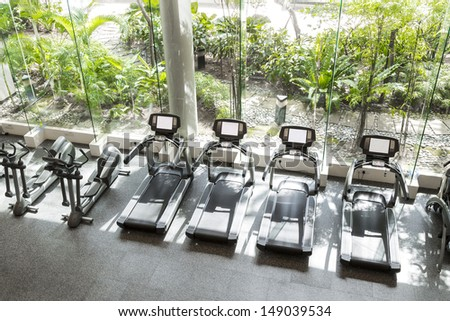 Interior of a club gym with a greenery in front. - stock photo