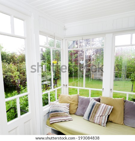 interior of a glass veranda with view to the garden - stock photo