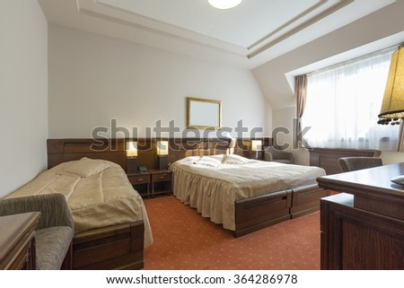 Interior of a hotel bedroom in the morning sunlight - stock photo