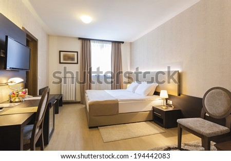 Interior Of A Hotel Bedroom With Framed Wall Mounted Tv